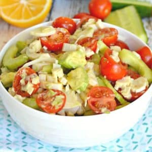 Bowl of avocado and hearts of palm salad with lemon in background