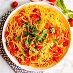 Serving bowl of pasta topped with fresh tomato basil sauce