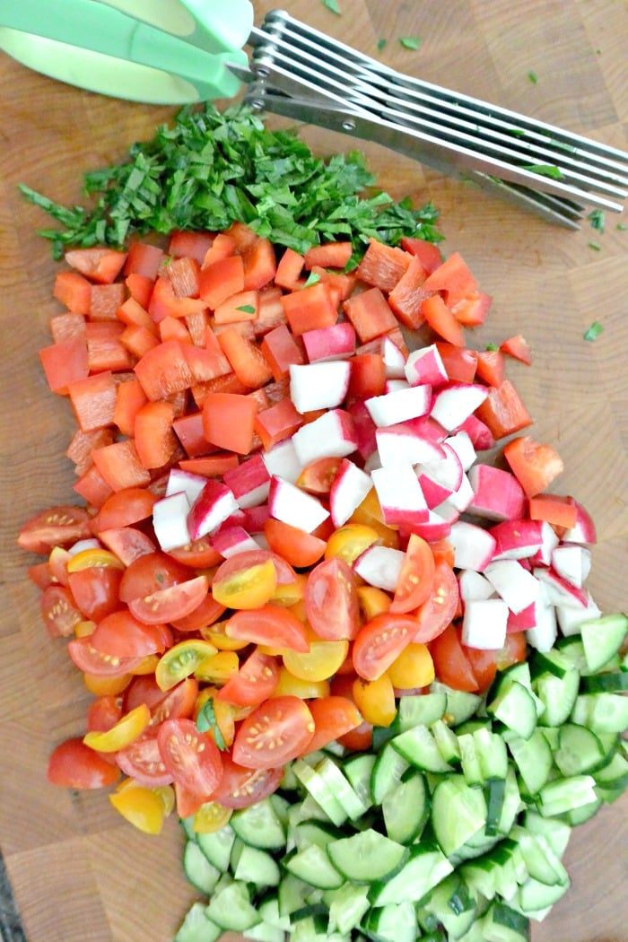 Chopped parsley, tomatoes, radishes, bell peppers, and cucumbers on a cutting board