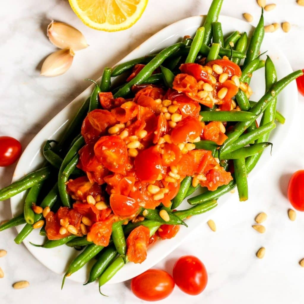 Platter of green beans topped with tomatoes and pine nuts