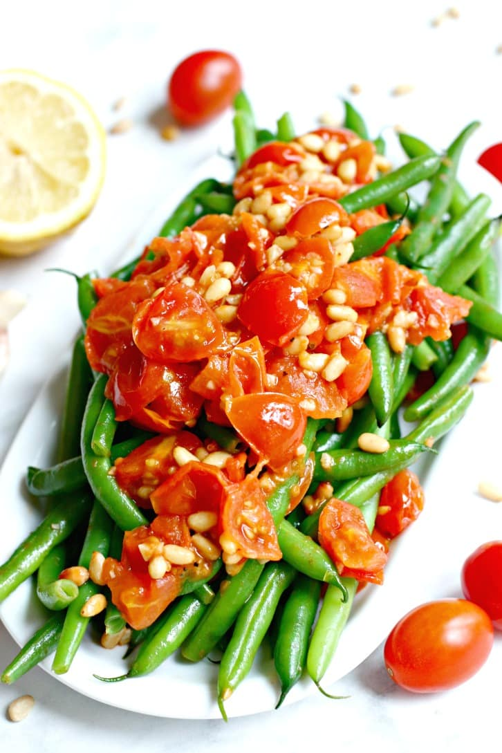 Serving platter of green beans topped with tomato and pine nut sauce