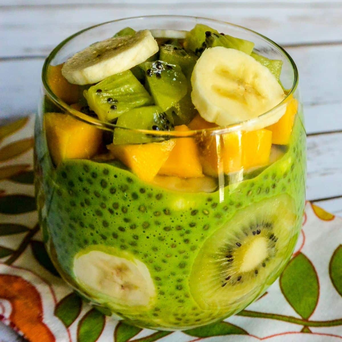 Green chia pudding with kiwi, mango, and banana in a glass