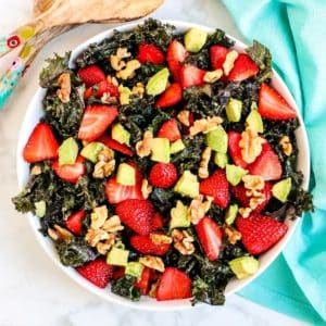 Overhead of serving bowl of kale salad topped with sliced strawberries, avocado cubes, and walnuts