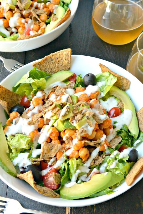 Two buffalo chickpea salads with forks and beverages
