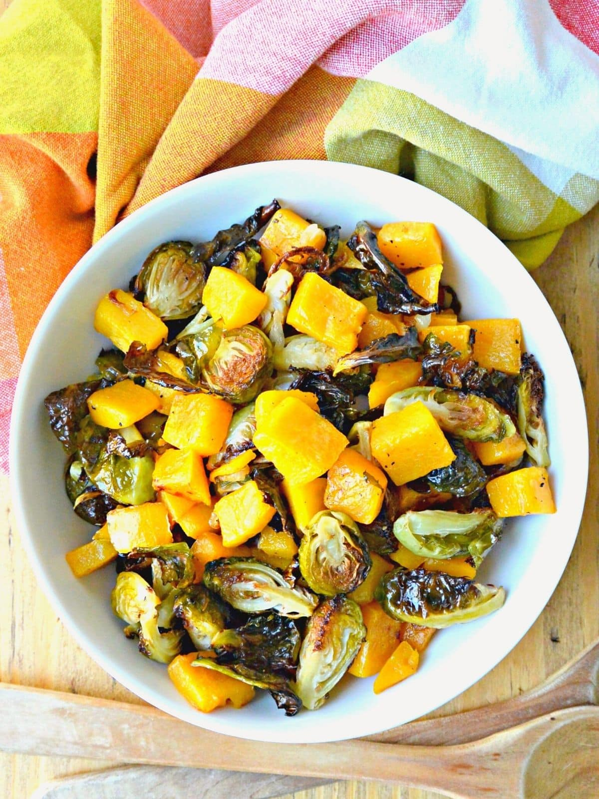 Bowl of roasted butternut squash and Brussels sprouts with an orange plaid napkin.