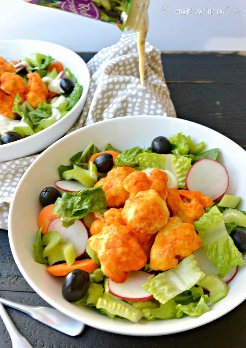Pouring vegan ranch dressing over Buffalo Cauliflower Bites Salad