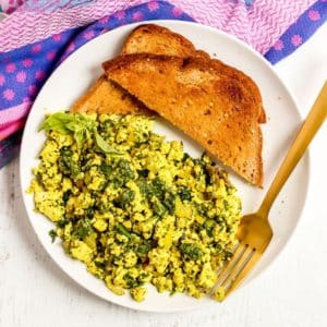 Plate of tofu scramble and toast with a gold fork
