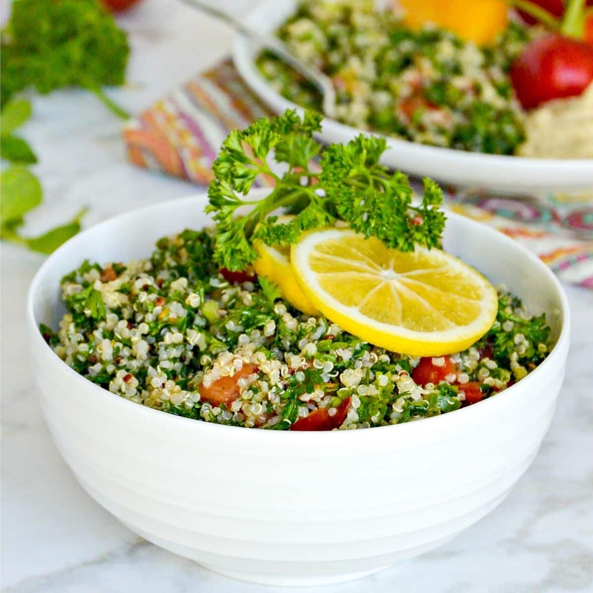 Bowl of quinoa tabbouleh salad garnished with sprig of parsley and slices or lemon
