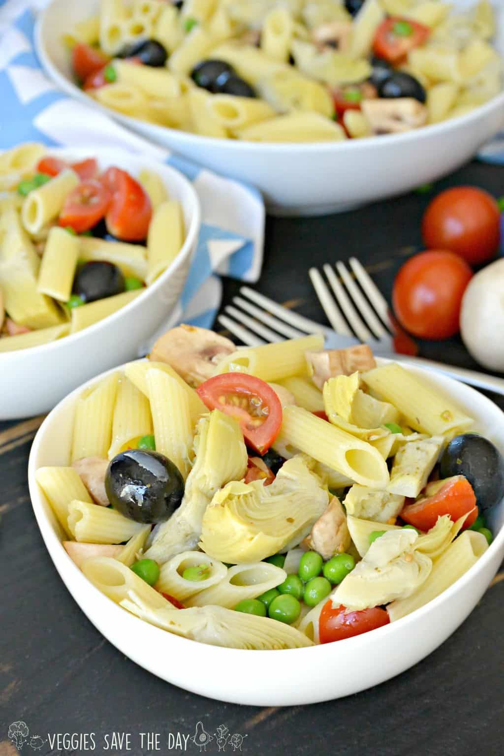 Pasta salad with gluten-free penne pasta, marinated artichoke hearts, peas, mushrooms, cherry tomatoes, and black olives.