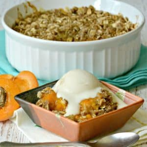 Small bowl with serving of apricot crisp topped with vanilla ice cream with fresh apricot and baking dish of dessert in the background