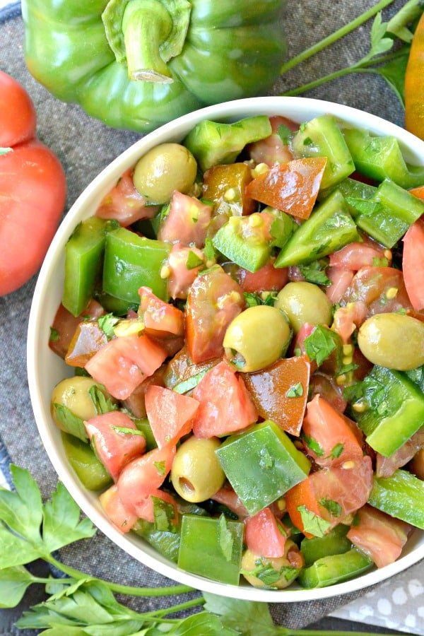 Overhead of Green Pepper Salad with Tomatoes surrounded by peppers, tomatoes, and fresh parsley