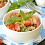 Bowl of bean and tomato salad garnished with sprig of fresh basil