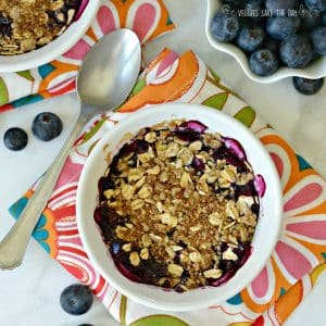 Blueberry crumble in a small ramekin with a spoon on the side