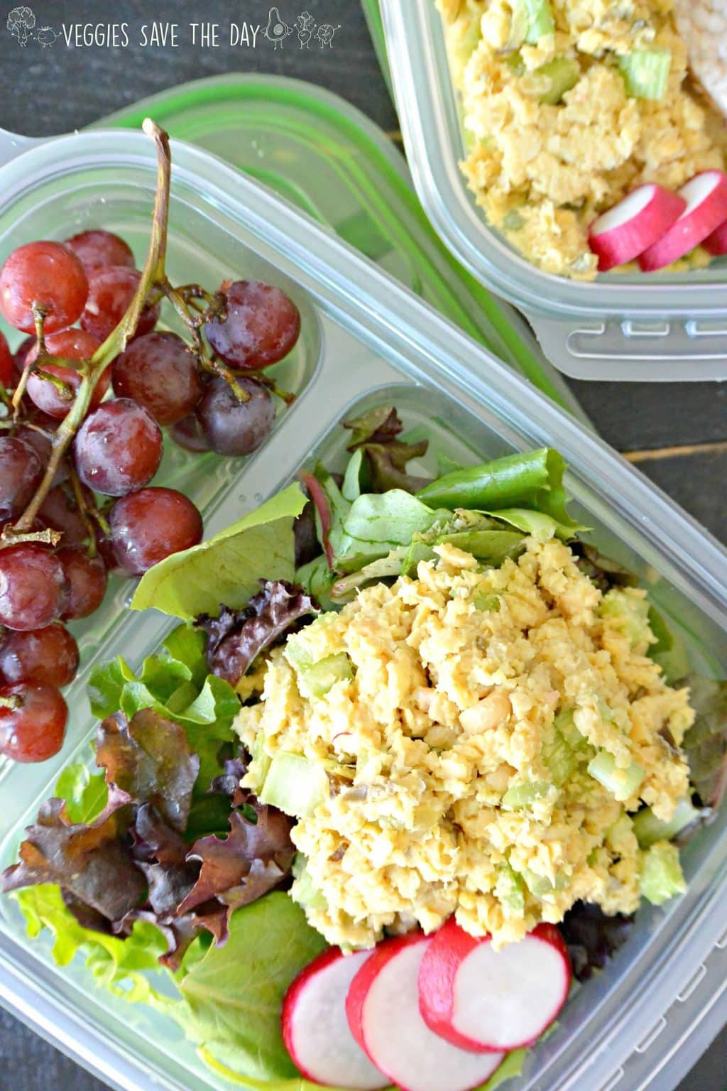 Vegan Tuna Salad packed for back-to-school or work lunches on a bed of mixed lettuce and a side of red grapes.