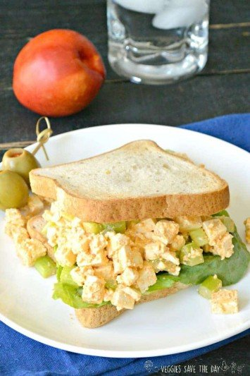 Sriracha Tofu Egg Salad sandwich served with fruit for lunch.