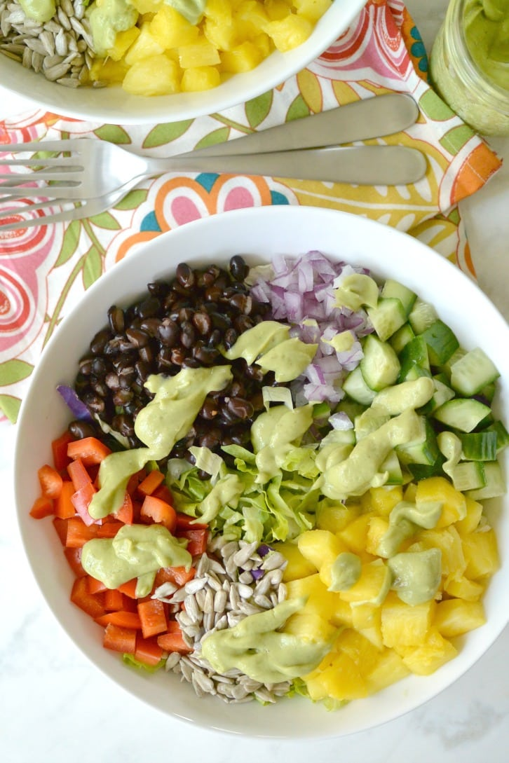 Black Bean Pineapple Salad made with cucumbers, red bell peppers, red onion, sunflower seeds, and oil-free avocado dressing.