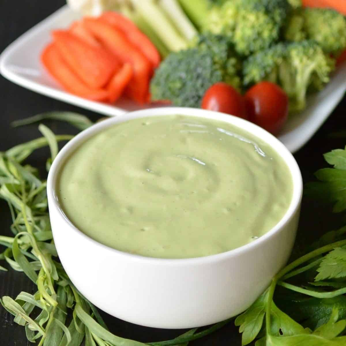 Bowl of Green Goddess Dressing with a platter of raw vegetables in the background