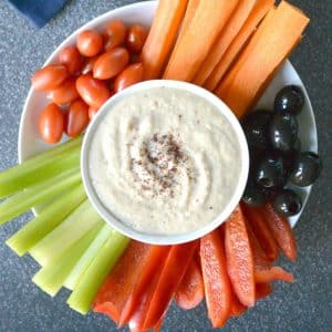 White Bean Dip in a bowl surrounded by carrots, celery, red bell pepper, black olives, and grape tomatoes