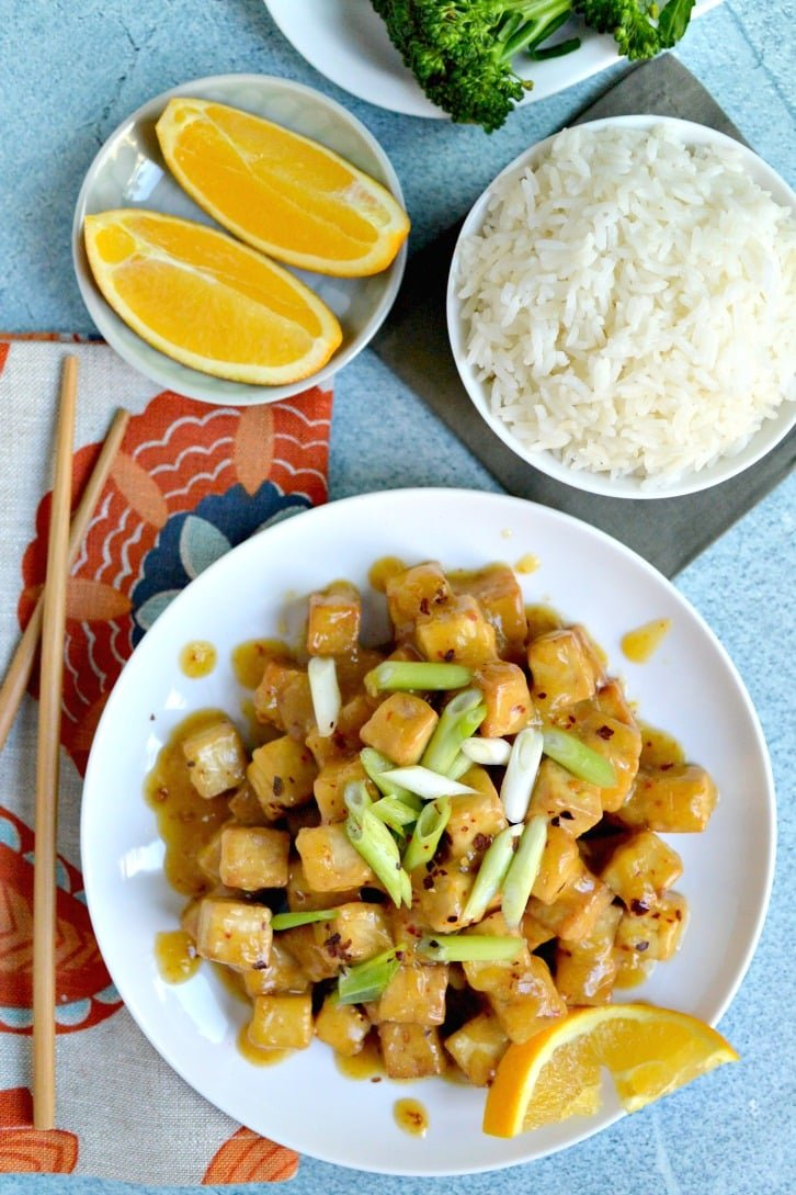 Air Fryer Orange Tofu (Oil-Free) served with steamed rice and orange wedges.