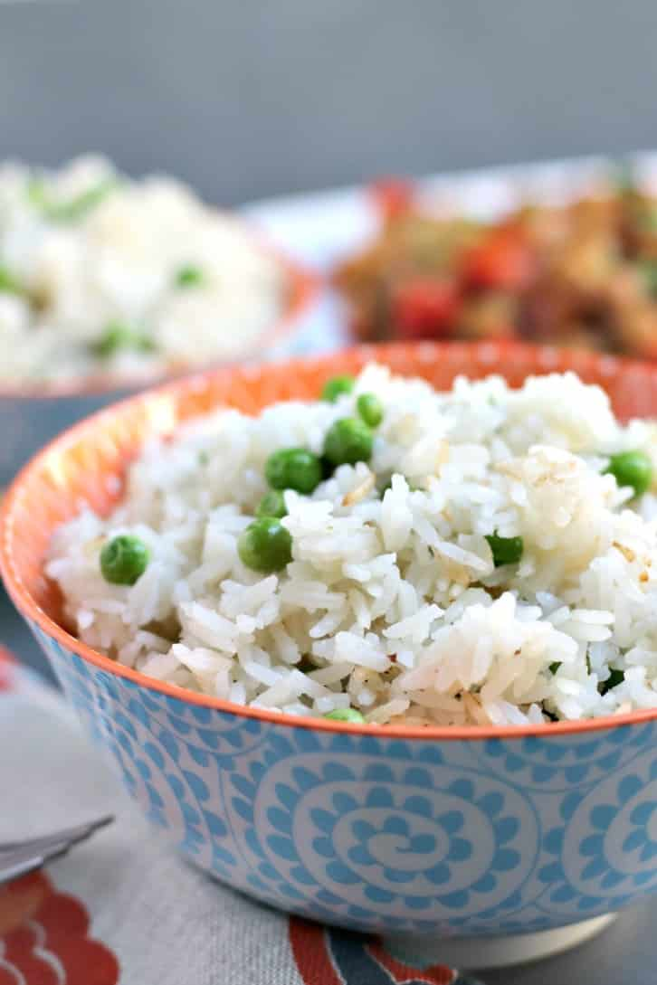 Serving bowl of Coconut Jasmine Rice (Instant Pot Recipe) with green peas in front of a platter of stir fry