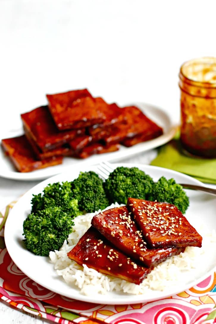 Baked Teriyaki Tofu served on rice with steamed broccoli with serving plate of teriyaki tofu and jar of teriyaki sauce in the background.