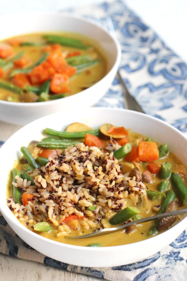 Green Bean Curry topped with brown rice and Quinoa with a fork in it.