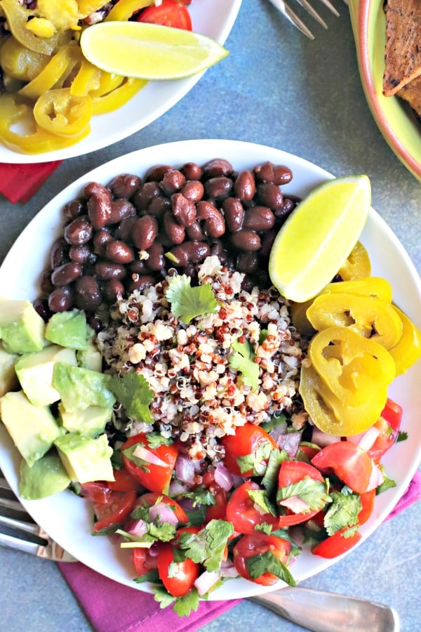 Quinoa Burrito Bowls are easy to assemble and delicious to eat. Cilantro lime quinoa, seasoned black beans, cherry tomato pico de gallo, pickled jalapenos, and diced avocado come together in a meal that's vegan, gluten-free, and oil-free. #quinoa #burritobowl #vegan #glutenfree #oilfree
