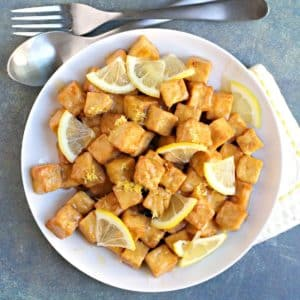 Plate of air fried tofu coated with lemon sauce and garnished with fresh lemon