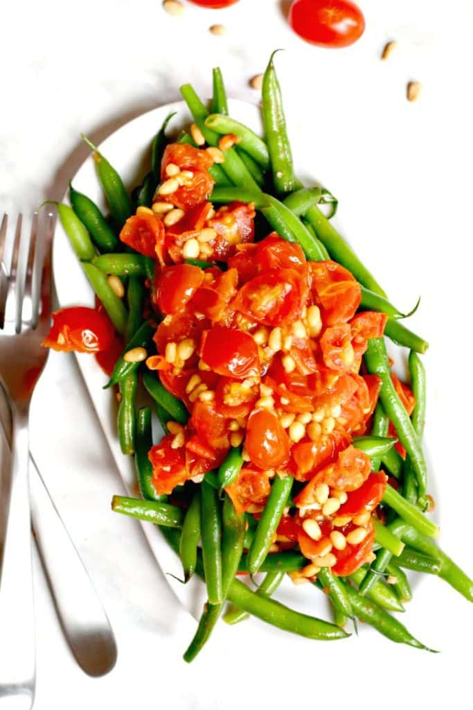 Overhead of sauteed green beans with tomato sauce topping and serving fork and spoon on the side