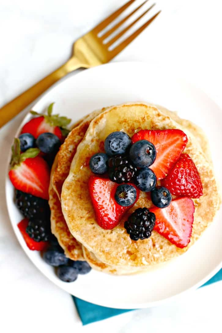 Vegan Banana Yogurt Pancakes topped with strawberries, blueberries, and blackberries