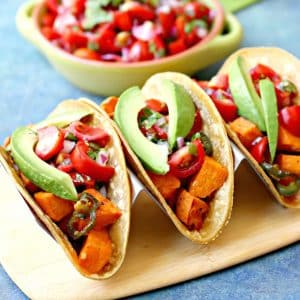Roasted Sweet Potato Tacos topped with pico de gallo and avocado slices (vegan and gluten-free)