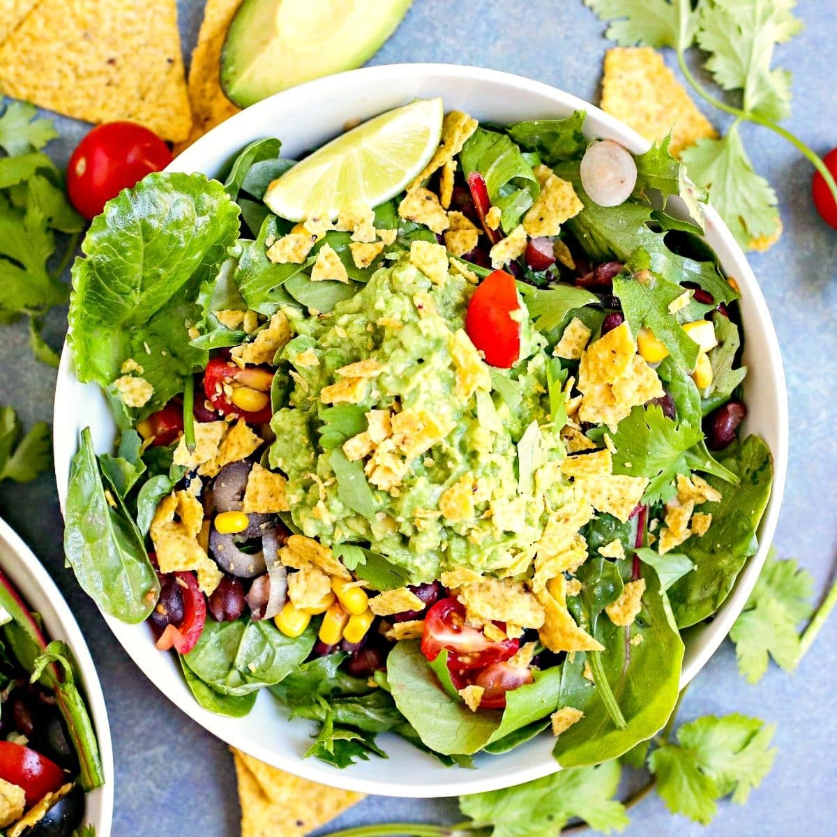 Bowl of salad topped with guacamole and crushed tortilla chips