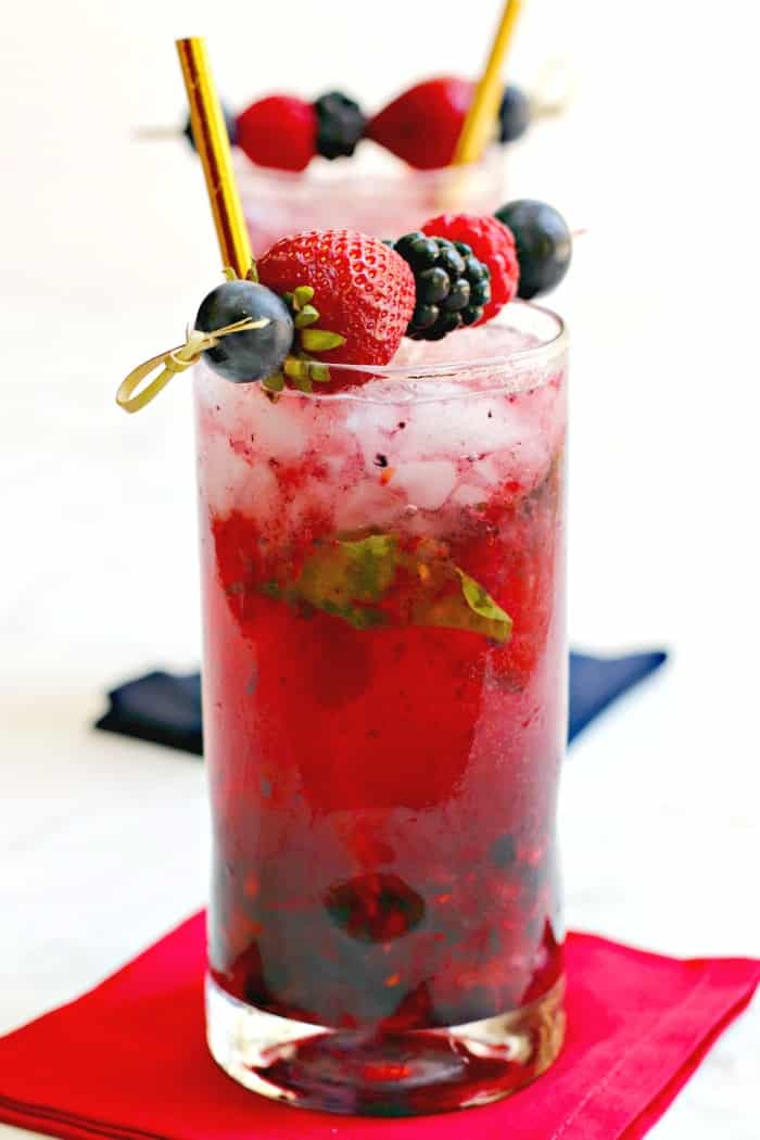 Berry Vodka Cocktail with gold straw and fresh berries garnish on a red napkin with another cocktail in the background