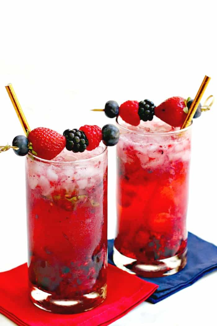 Easy Berry Vodka Cocktails with gold straws on red and blue napkins