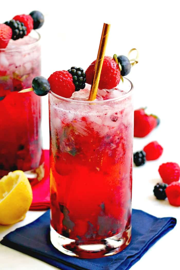 Cocktails garnished with fresh berries and gold paper straws
