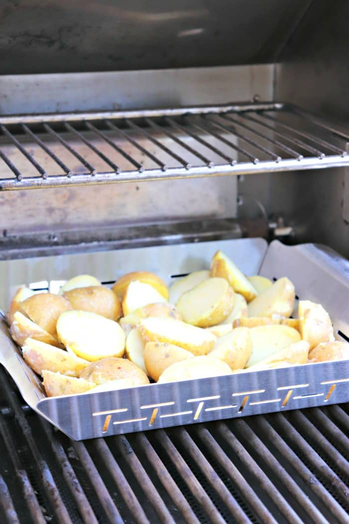 Potatoes in a grill basket on an outdoor barbecue grill