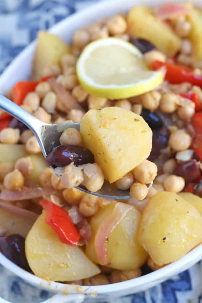 Close up of serving spoon filled with Greek Lemon Roasted Potatoes with Chickpeas
