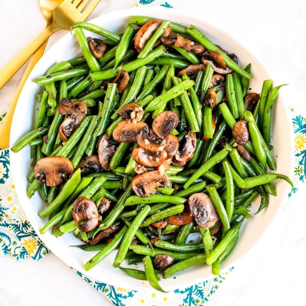 Serving bowl of green beans and mushrooms with gold utensils