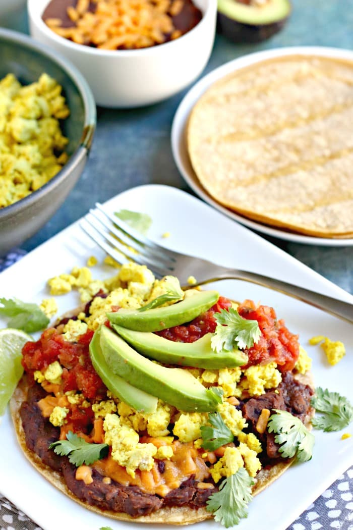 Tofu Scramble Breakfast Tostada with tortillas and toppings in the background