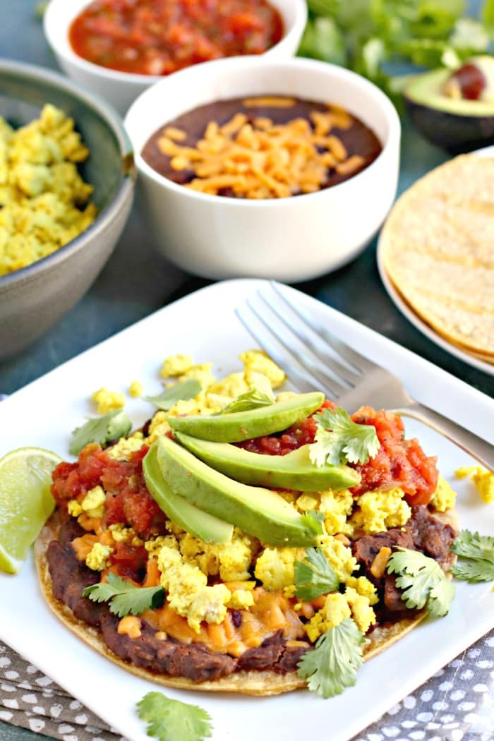 Tofu Scramble Breakfast Tostadas with corn tortillas, refried black beans, vegan cheese, salsa, avocado slices, and cilantro