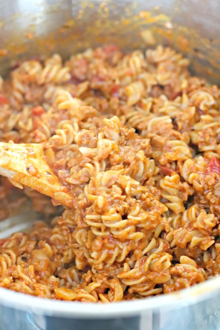 Mixing the cooked rotini pasta into the sauce made with onion, MorningStar Farms Chorizo Crumbles, fire roasted diced tomatoes, and non-dairy shredded pepper jack cheese