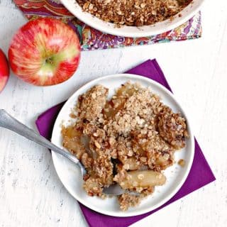 Apple crisp on a plate with an apple in the background