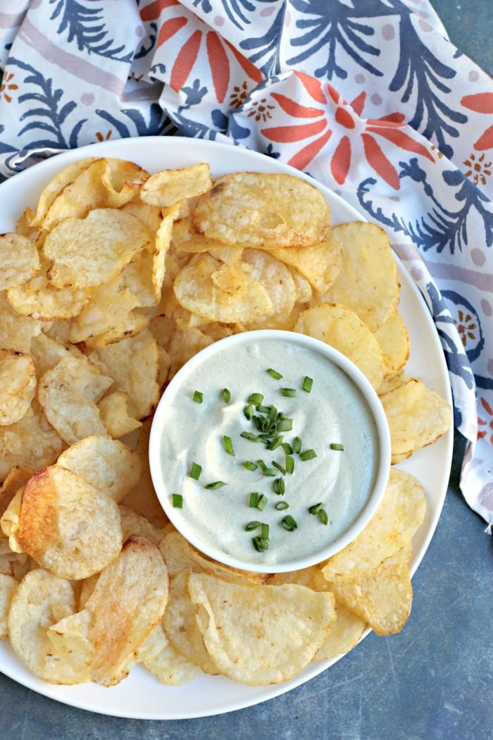 Overhead of plate of potato chips with bowl of Vegan Sour Cream Dip