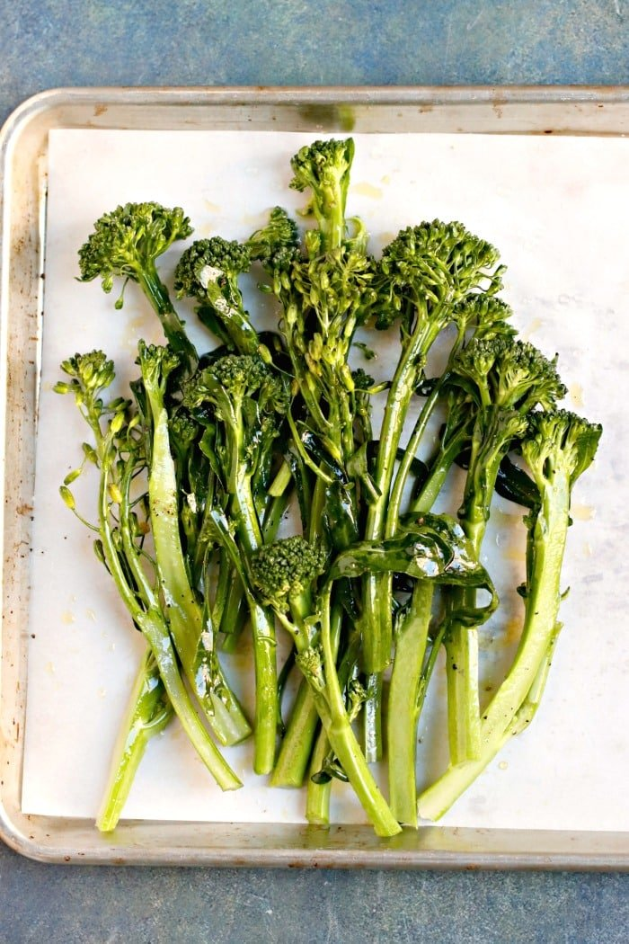 Broccolini tossed with olive oil, lemon juice, and salt and pepper on a roasting pan ready to go in the oven