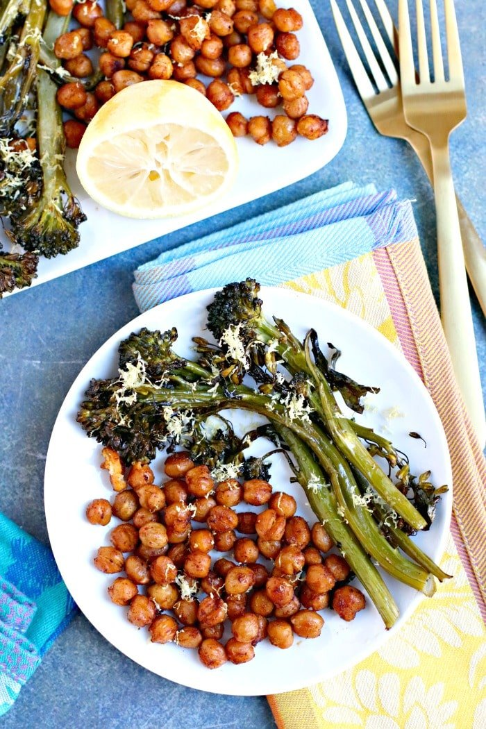 Overhead of plate with Roasted Broccolini and Chickpeas and forks with serving dish in the background