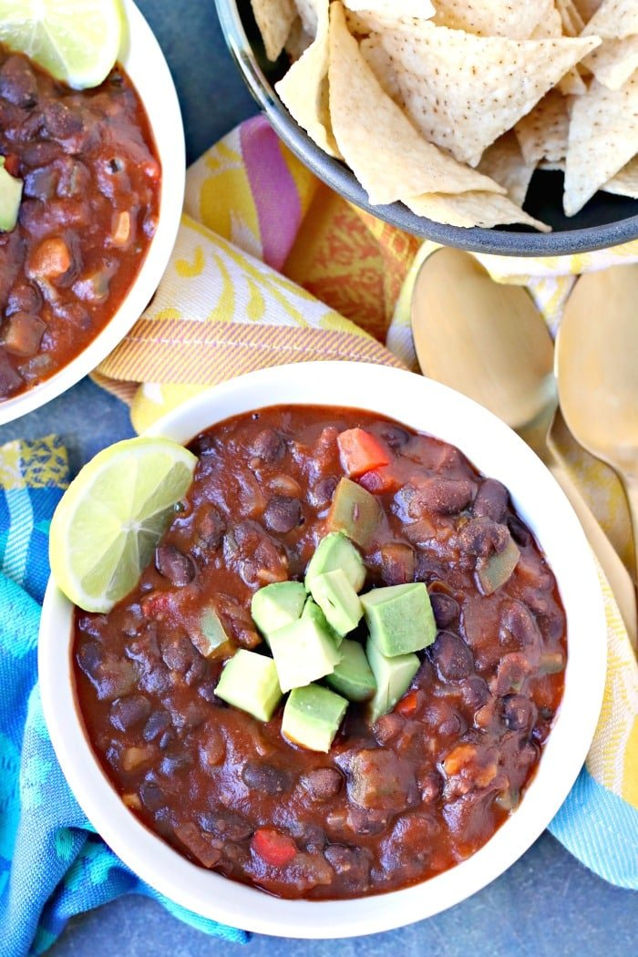 Overhead of bowl of Easy Black Bean Chili topped with cubed avocado and a slice of lime