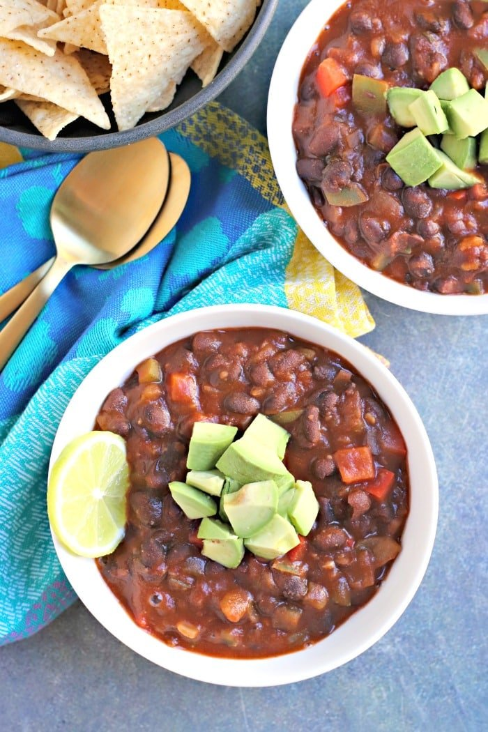 Overhead of two bowls of Easy Black Bean Chili with gold spoons and bowl of tortilla chips