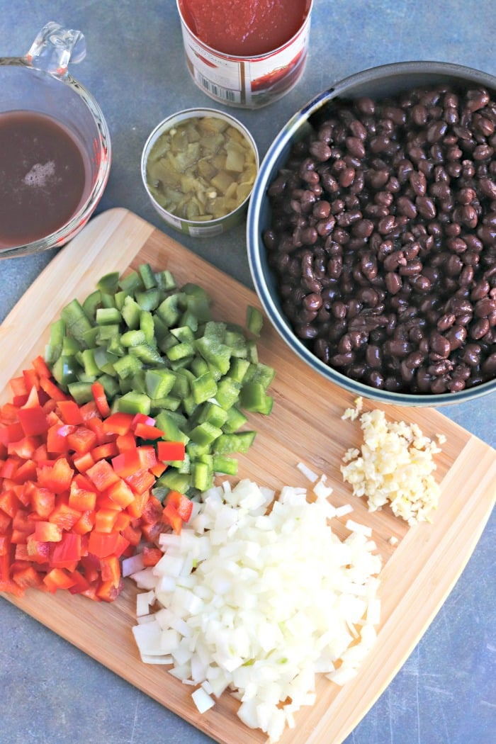 Ingredients for making Easy Black Bean Chili: black beans, garlic, onion, red and green bell pepper, liquid from the canned beans, diced canned chilies, and tomato sauce