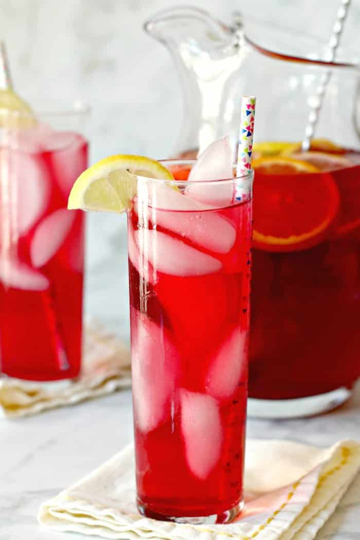 Tall glass of Spiked Iced Tea with pitcher and another glass in the background