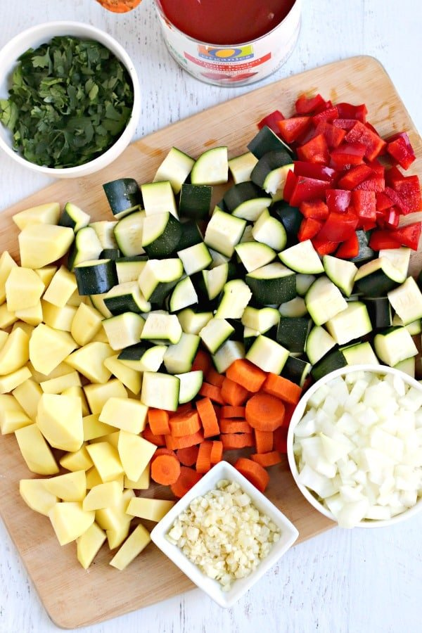 Cutting board with diced zucchini, red bell pepper, onion, carrots, garlic, potatoes, and parsley and a can of tomatoes